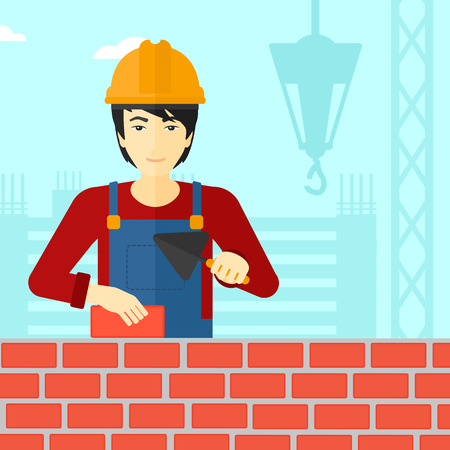 An asian bricklayer with a spatula and a brick in hands on a background of construction site vector flat design illustration. Square layout. Illustration