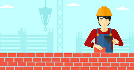 brick and mortar: An asian bricklayer with a spatula and a brick in hands on a background of construction site vector flat design illustration. Horizontal layout.