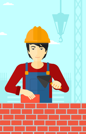 brick and mortar: An asian bricklayer with a spatula and a brick in hands on a background of construction site vector flat design illustration. Vertical layout.
