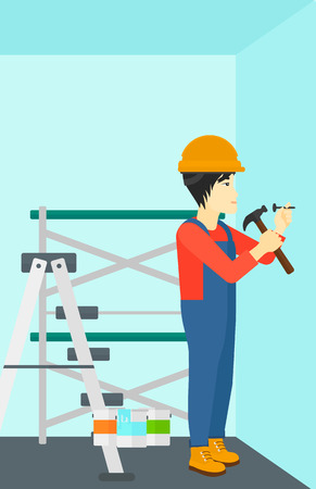An asian man hitting a nail in the wall with a hummer on a background of room with paint cans and ladder vector flat design illustration. Vertical layout.