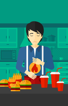 reflux: An asian man standing in the kitchen in front of table full of junk food and suffering from heartburn vector flat design illustration. Vertical layout.