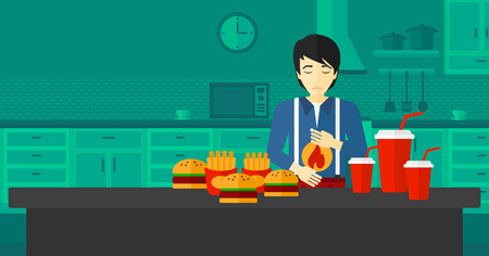 fire in the belly: An asian man standing in the kitchen in front of table full of junk food and suffering from heartburn vector flat design illustration. Horizontal layout.