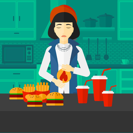 reflux: An asian woman standing in the kitchen in front of table full of junk food and suffering from heartburn vector flat design illustration. Square layout.