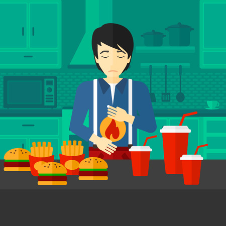 reflux: An asian man standing in the kitchen in front of table full of junk food and suffering from heartburn vector flat design illustration. Square layout. Illustration