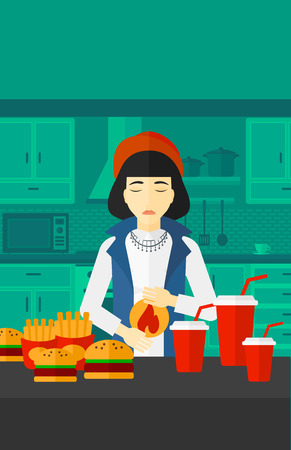 fire in the belly: An asian woman standing in the kitchen in front of table full of junk food and suffering from heartburn vector flat design illustration. Vertical layout.