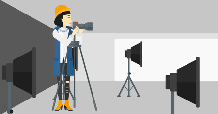 lighting equipment: An asian photographer working with camera on the background of photo studio with lighting equipment vector flat design illustration. Horizontal layout.