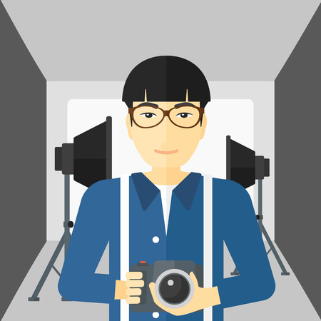 lighting equipment: An asian man holding a camera on the background of photo studio with lighting equipment vector flat design illustration. Square layout.