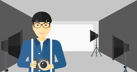 lighting equipment: An asian man holding a camera on the background of photo studio with lighting equipment vector flat design illustration. Horizontal layout.