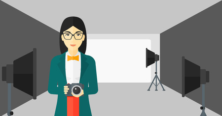 lighting equipment: An asian woman holding a camera on the background of photo studio with lighting equipment vector flat design illustration. Horizontal layout.