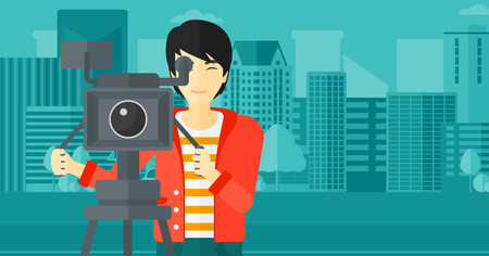 cinematographer: An asian cameraman with the beard looking through movie camera on a city background vector flat design illustration. Horizontal layout. Illustration