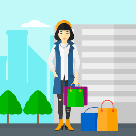 buyers: An asian woman standing with some shopping bags in hand and some bags on the ground on a city background vector flat design illustration. Square layout.