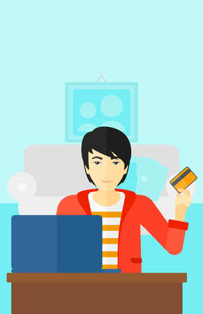 asian man laptop: An asian man sitting in front of laptop with credit card in hand and making purchases online on the background of living room vector flat design illustration. Vertical layout.