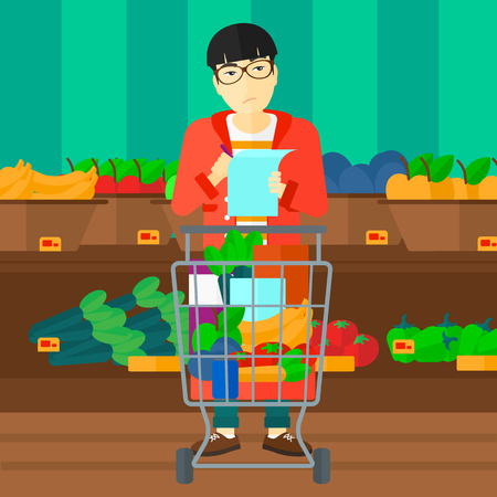 supermarket trolley: A thoughtful asian man standing with full supermarket trolley and holding a shopping list in hands on the background of shelves with vegetables and fruits in supermarket vector flat design illustration. Square layout.