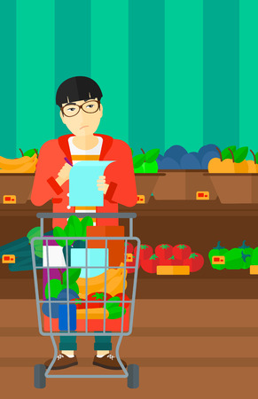 supermarket trolley: A thoughtful asian man standing with full supermarket trolley and holding a shopping list in hands on the background of shelves with vegetables and fruits in supermarket vector flat design illustration. Vertical layout. Illustration