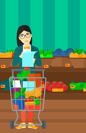 supermarket trolley: A thoughtful asian woman standing with full supermarket trolley and holding a shopping list in hands on the background of shelves with vegetables and fruits in supermarket vector flat design illustration. Vertical layout.