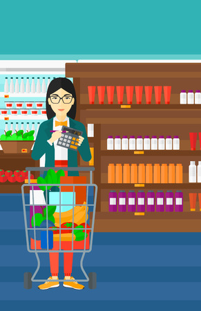 woman shopping cart: An asian woman standing near shopping cart and holding a calculator in hands on the background of supermarket shelves with products vector flat design illustration. Vertical layout.
