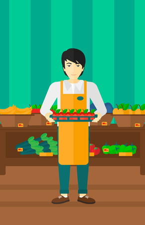 shop assistant: An asian man holding a box with apples on the background of shelves with vegetables and fruits in supermarket vector flat design illustration. Vertical layout.
