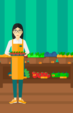 mujer en el supermercado: An asian woman holding a box with apples on the background of shelves with vegetables and fruits in supermarket vector flat design illustration. Vertical layout. Vectores