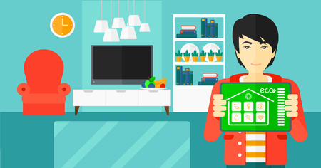 An asian man holding a tablet computer with smart home application on a screen on the background of modern  living room vector flat design illustration. Horizontal layout.