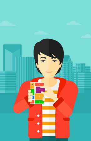 repurpose: An asian man holding modular phone on a city background vector flat design illustration. Vertical layout.