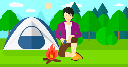 forest trees: An asian man kindling a fire on the background of camping site with tent vector flat design illustration. Horizontal layout.