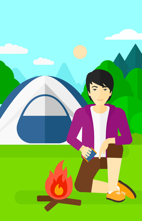 An asian man kindling a fire on the background of camping site with tent vector flat design illustration. Vertical layout. Vettoriali