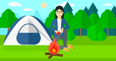 kindle: An asian woman kindling a fire on the background of camping site with tent vector flat design illustration. Horizontal layout. Illustration