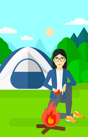 An asian woman kindling a fire on the background of camping site with tent vector flat design illustration. Vertical layout. Vettoriali