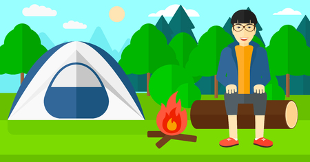 An asian man sitting on a log near the fire on the background of camping site with tent vector flat design illustration. Horizontal layout. Vettoriali