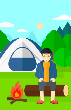 An asian man sitting on a log near the fire on the background of camping site with tent vector flat design illustration. Vertical layout.