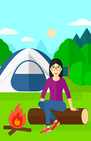 An asian woman sitting on a log near the fire on the background of camping site with tent vector flat design illustration. Vertical layout.