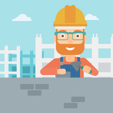 bricklayer: A hipster bricklayer with a spatula and a brick in hands on a background of construction site vector flat design illustration. Square layout.