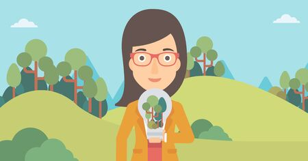 A woman standing on the background of green forest and holding in hands a big lightbulb with trees inside vector flat design illustration. Horizontal layout.