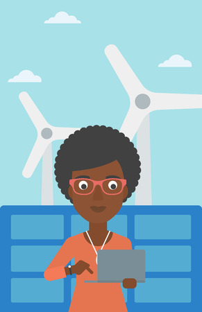 ecologically: An african-american woman holding a laptop in hands on a background with solar pannels and wind turbins vector flat design illustration. Vertical layout. Illustration