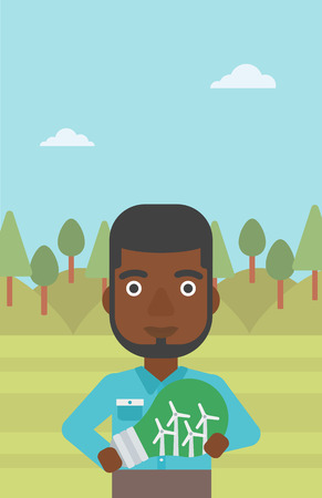 An african-american man standing on the background of green forest and holding in hands a big light bulb with small wind turbines inside vector flat design illustration. Vertical layout. Vettoriali