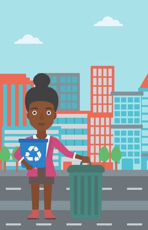 An african-american woman standing with a recycle bin in hand and another bin on the ground on a city background vector flat design illustration. Vertical layout.