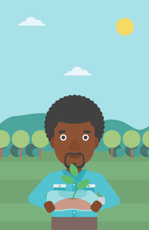 growing inside: An african-american man standing on the background of mountain landscape and holding in hands a plastic bottle with a small plant growing inside vector flat design illustration. Vertical layout. Illustration