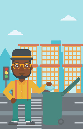 An african-american man throwing a trash into a green bin on a city background vector flat design illustration. Vertical layout. Vettoriali