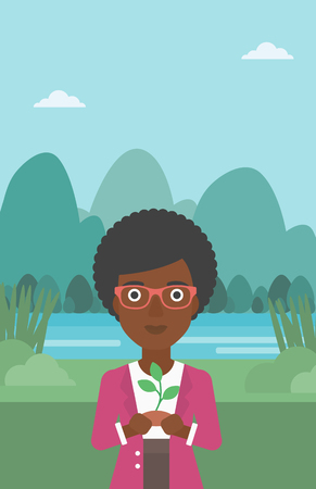 hands holding plant: An african-american woman holding in hands a small plant in soil on the background of landscape with mountains and river vector flat design illustration. Vertical layout.