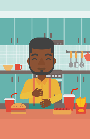 fire in the belly: An african-american man standing in the kitchen in front of table full of junk food and suffering from heartburn vector flat design illustration. Vertical layout.