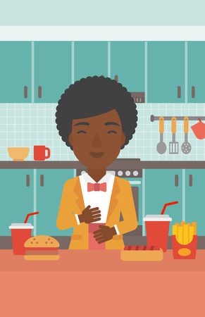 fire in the belly: An african-american woman standing in the kitchen in front of table full of junk food and suffering from heartburn vector flat design illustration. Vertical layout.