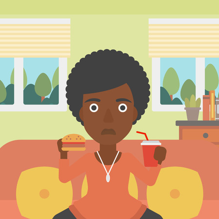 An african-american woman sitting on a sofa while eating hamburger and drinking soda on the background of living room vector flat design illustration. Square layout.