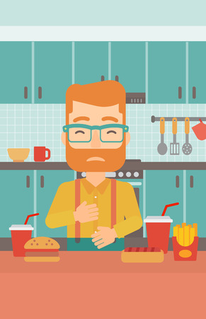 A hipster man with the beard standing in the kitchen in front of table full of junk food and suffering from heartburn vector flat design illustration. Vertical layout.