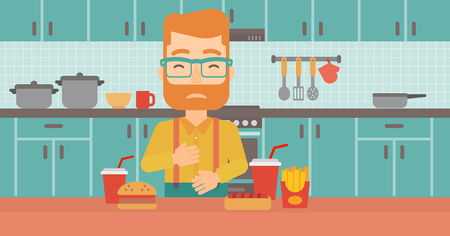 fire in the belly: A hipster man with the beard standing in the kitchen in front of table full of junk food and suffering from heartburn vector flat design illustration. Horizontal layout.