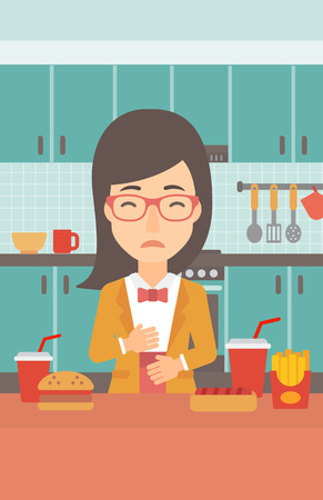 fire in the belly: A woman standing in the kitchen in front of table full of junk food and suffering from heartburn vector flat design illustration. Vertical layout.
