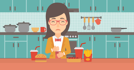 reflux: A woman standing in the kitchen in front of table full of junk food and suffering from heartburn vector flat design illustration. Horizontal layout. Illustration