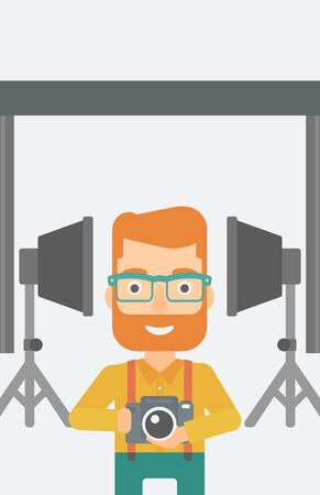 A hipster man with the beard holding a camera on the background of photo studio with lighting equipment vector flat design illustration. Vertical layout.