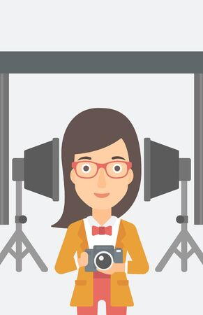 A woman holding a camera on the background of photo studio with lighting equipment vector flat design illustration. Vertical layout.