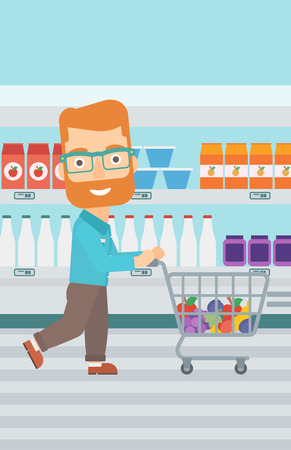 A hipster man with the beard pushing a supermarket cart with some goods in it on the background of supermarket shelves with products vector flat design illustration. Vertical layout.