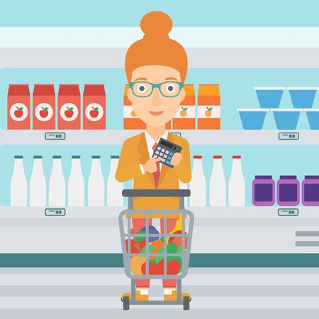 A woman standing near shopping cart and holding a calculator in hands on the background of supermarket shelves with products vector flat design illustration. Square layout. 일러스트